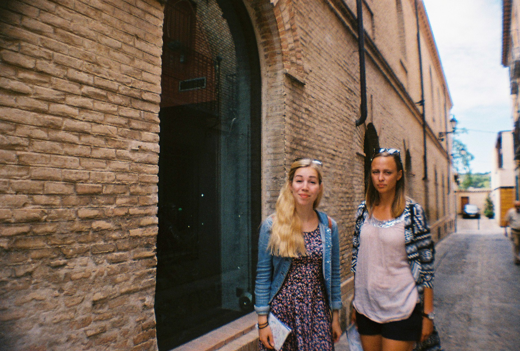 Girls standing in narrow cobblestone street