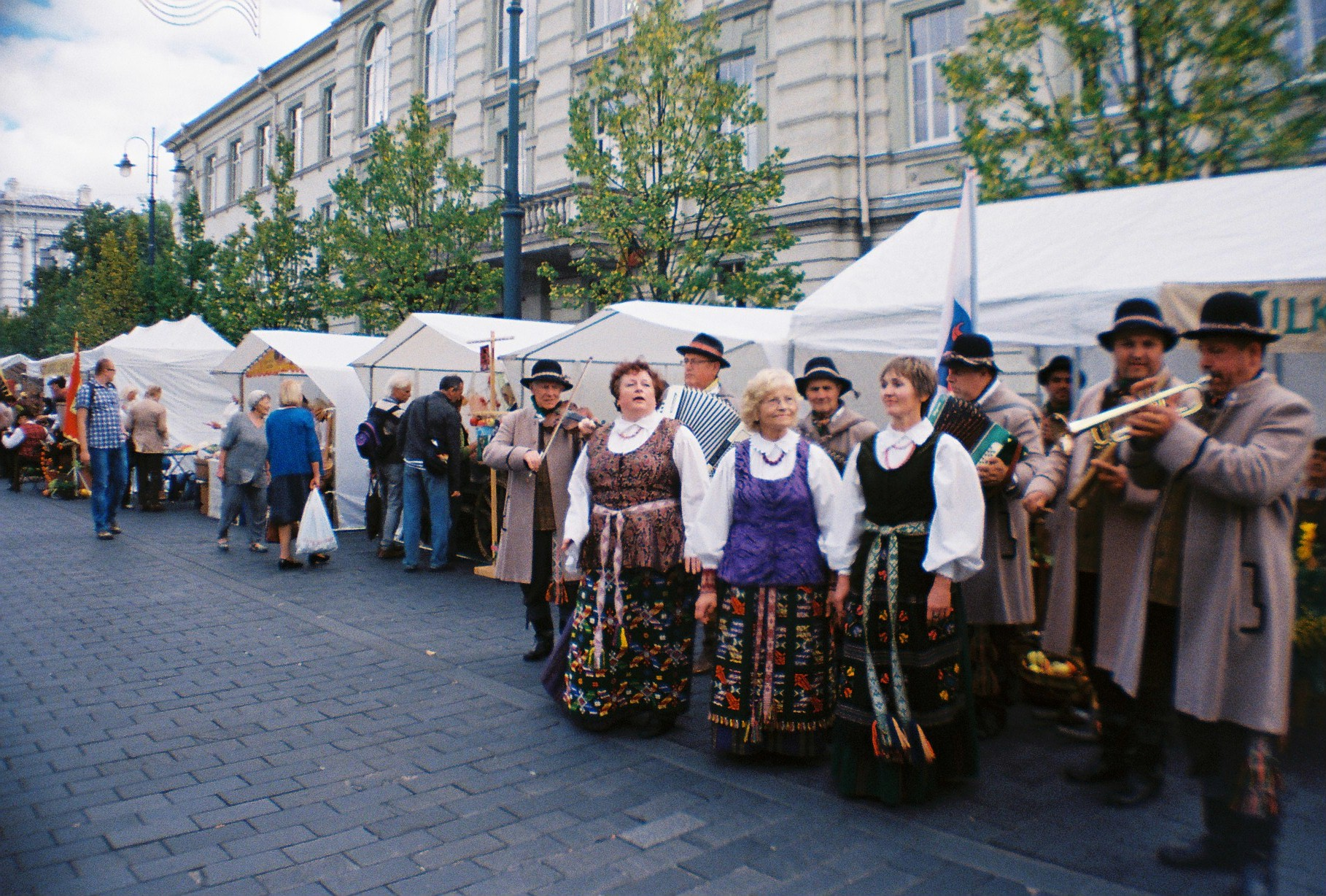 Women in traditional outfits outside open-air market